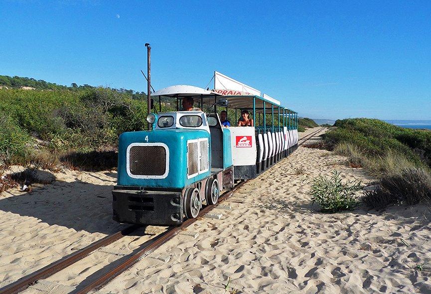 O comboio do Transpraia vai pela areia e te leva para as 21 praias da Caparica.