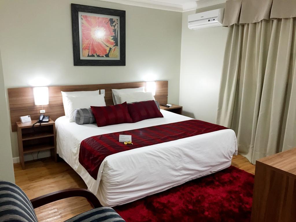 Quarto do hotel Açores Premium, em Porto Alegre. Cama de casal com lençoies brancps e almofadas vinho. Tapete vermelho e preto nos pés da cama. o lado direito há uma cortina bege. Em cima da cama um quadro com grvura vermelha, preta e bege.