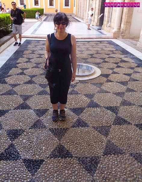 A estrangeira Fabia num chão geométrico de pedras.
